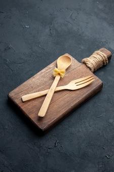 Vista dal basso incrociate cucchiaio di legno e forchetta sul tagliere di legno sulla superficie scura