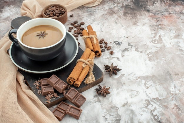 Bottom view cup of coffee chocolate cinnamon sticks on wood board roasted coffee beans in wooden bowl anises on table copy place