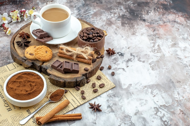 Bottom view cup of coffee cookies bowl with coffee beans chocolate cinnamon sticks anises on wood board on table with free space