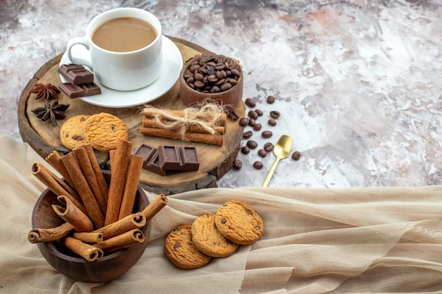 Bottom view cup of coffee cookies bowl with coffee beans chocolate cinnamon sticks in bowl anise stars on wood board on table with free space