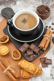 コーヒーチョコレートシナモンの底面図カップは、テーブルの上の木製のボウルにある木の板のローストコーヒー豆にクッキーを貼り付けます