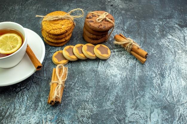 여유 공간이 있는 회색 테이블에 밧줄 계피 막대기로 묶인 레몬과 계피 비스킷 쿠키로 맛을 낸 차 한 잔