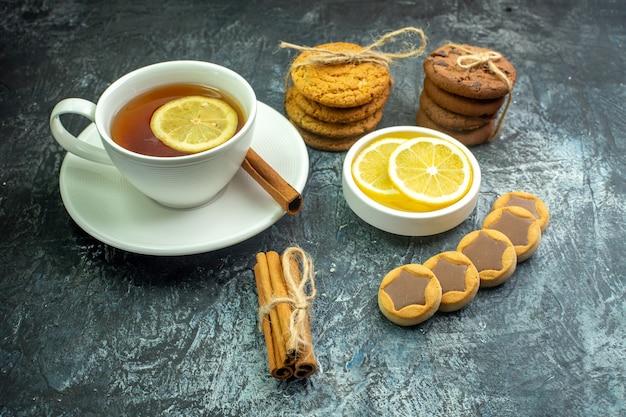회색 테이블에 있는 그릇에 로프 계피 스틱 레몬 조각으로 묶인 초콜릿 쿠키와 레몬과 계피 비스킷으로 맛을 낸 차 한 잔