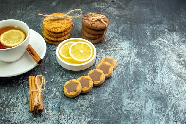 회색 테이블 무료 장소에 로프 계피 스틱 레몬 조각으로 묶인 초콜릿 쿠키와 함께 레몬 비스킷으로 맛을 낸 차 한 잔