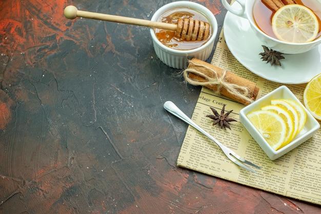 작은 그릇 포크에 있는 차 레몬 조각의 하단 뷰 컵 계피 스틱 아니스 꿀과 꿀 스틱은 복사 장소가 있는 짙은 빨간색 테이블에 있는 신문 메모장에 있는 그릇에 있습니다.
