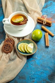 Вид снизу чашка чая с лимоном и корицей, бежевое печенье с шалью, лимон на сине-красной поверхности