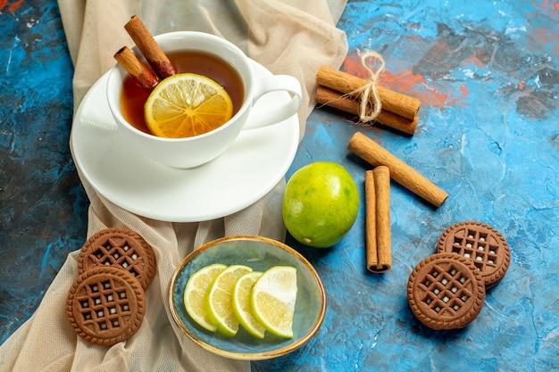 Вид снизу чашка чая с лимоном и корицей, бежевое печенье с шалью, лимон на сине-красном столе