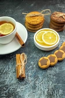 회색 테이블에 로프 계피 스틱으로 묶인 초콜릿 쿠키와 레몬과 계피 비스킷을 곁들인 차 한 잔