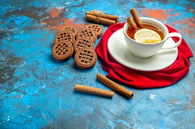 Вид снизу чашка чая с лимонным и коричным красным шалевым печеньем на синей красной поверхности