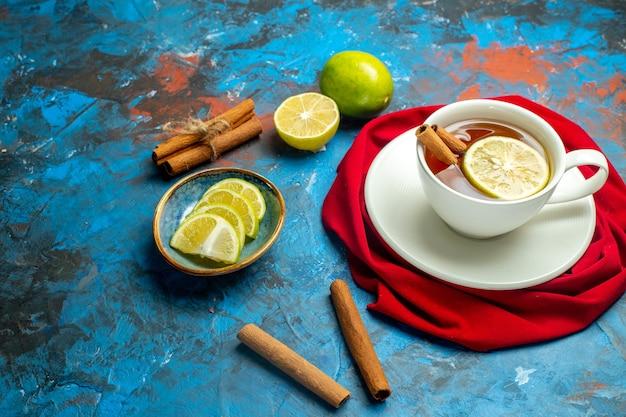 Вид снизу чашка чая с лимоном и красной шалью с корицей на синей красной поверхности