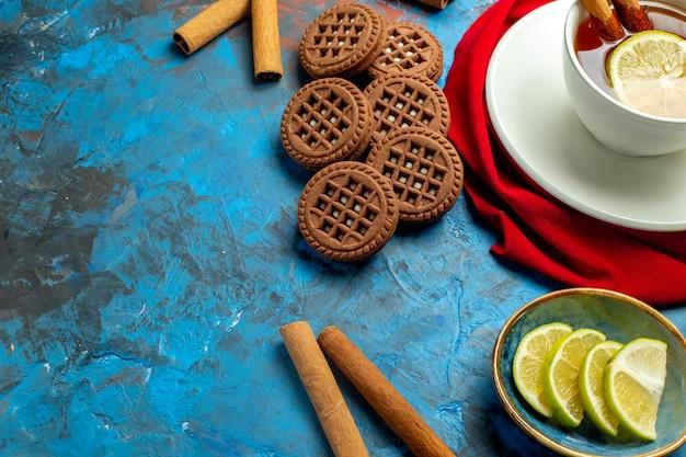 Вид снизу чашка чая с лимоном и красной шалью с корицей на сине-красной поверхности со свободным местом