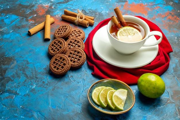 Вид снизу чашка чая с красной шалью лимона и корицы на синей красной поверхности