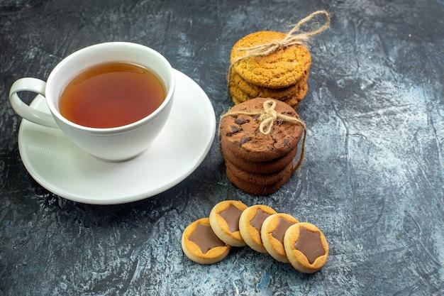 Vista dal basso di una tazza di biscotti da tè legati con una corda sul tavolo grigio posto libero