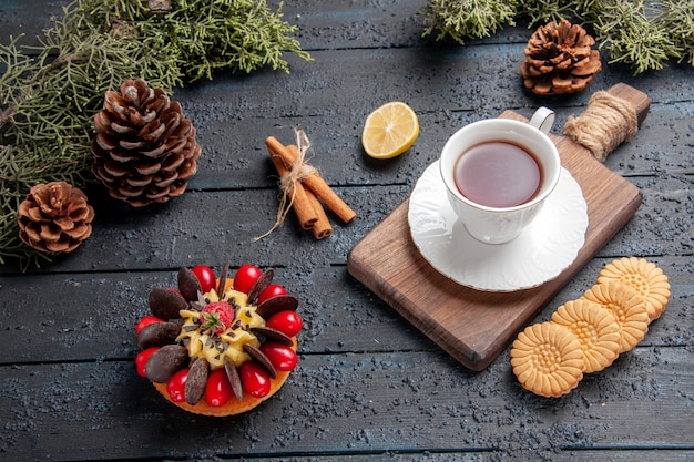 Bottom view a cup of tea on chopping board slice of lemon pinecones cookies cinnamon and berry cake on dark wooden background