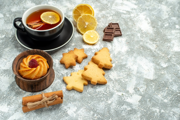 Bottom view a cup of tea lemon slices cinnamon sticks cookies chocolate on grey surface free space