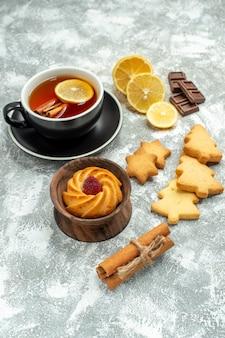 Bottom view a cup of tea lemon slices cinnamon sticks cookies chocolate on grey surface