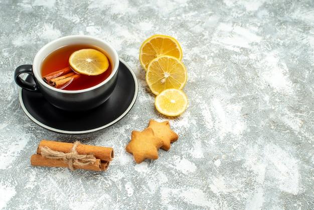Vista dal basso una tazza di tè, fette di limone, bastoncini di cannella su una superficie grigia con spazio libero