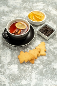 Bottom view a cup of tea with lemon and cinnamon sticks biscuits bowl with chocolate and lemon slices on grey surface