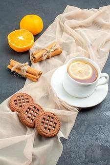 Bottom view a cup of tea with lemon cinnamon sticks cookies on beige shawl orange on dark surface