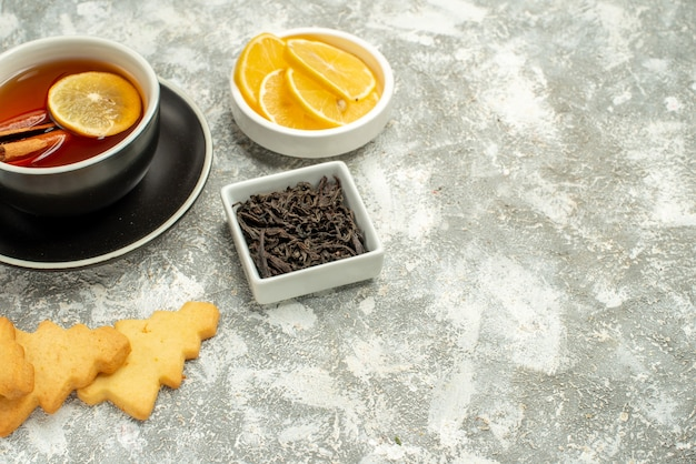 Bottom view a cup of tea with lemon slices and cinnamon sticks biscuits bowl with chocolate on grey surface free space