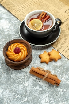 Bottom view a cup of tea with lemon slices and cinnamon sticks on newspaper biscuits on grey surface