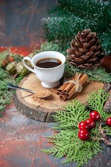 Vista dal basso una tazza di tè su tavola di legno bastoncini di cannella pigna al buio