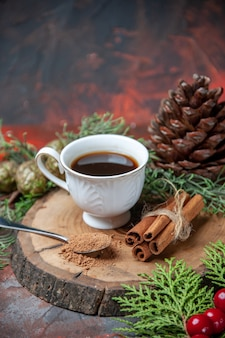 Bottom view a cup of tea on wood board cinnamon sticks pinecone on dark