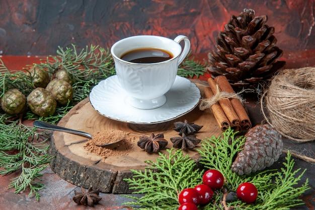 Bottom view a cup of tea on wood board cinnamon sticks pinecones anises on dark