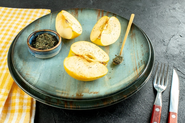 Vista dal basso tagliate mele menta secca in una ciotola cucchiaio di legno sul piatto coltello e una forchetta asciugamano da cucina giallo su fondo scuro