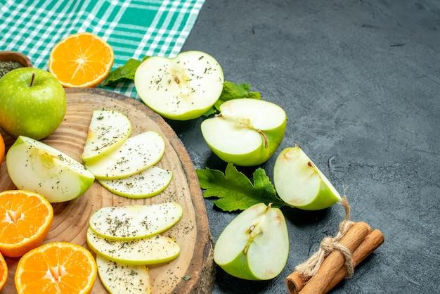 Vista dal basso tagliare mele e mandarini su tavola di legno bastoncini di cannella legati con corda su tovaglia verde su tavolo scuro posto libero