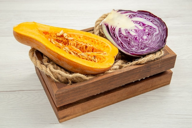 Bottom view cut butternut squash cut red cabbage rope in wooden box on white table