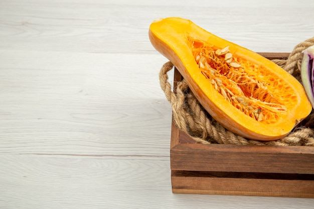 Bottom view cut butternut squash in wooden box on white table with free space