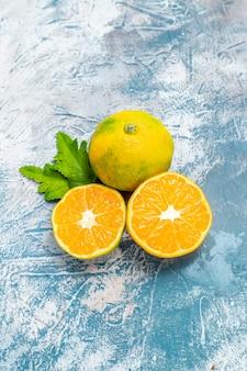 Вид снизу нарезанные мандарины на синей белой поверхности свободного пространства