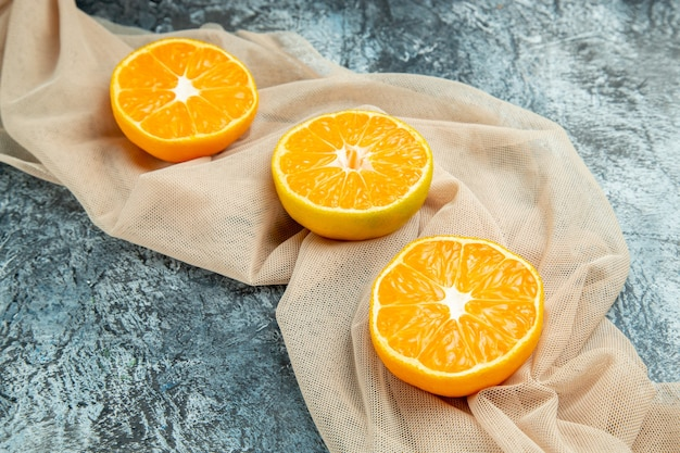 Bottom view cut oranges on beige shawl on dark surface