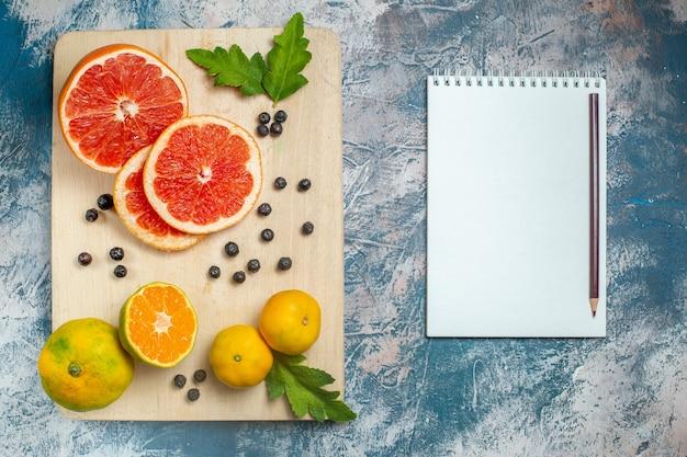 Vista dal basso tagliare arance e pompelmi sul taccuino del tagliere e matita su superficie bianca blu