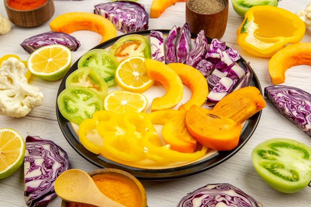 Vista dal basso tagliare frutta e verdura zucca cachi cavolo rosso limone pomodori verdi cavolfiore peperoni sul piatto rotondo varie spezie in piccole ciotole sul tavolo