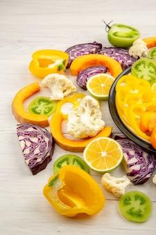 Vista dal basso tagliare frutta e verdura zucca peperoni gialli cachi cavolo rosso pomodori verdi sulla banda nera sulla tavola di legno