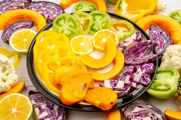 Bottom view cut vegetables and fruits yellow bell peppers pumpkin persimmon red cabbage lemon green tomatoes on platter on table
