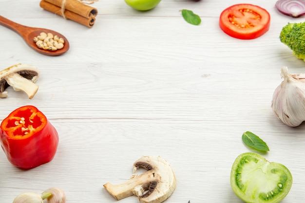 Вид снизу нарезанные овощи деревянной ложкой, палочки корицы и другие продукты на сером столе со свободным пространством