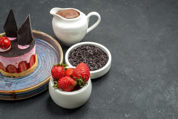 Vista dal basso deliziosa cheesecake con fragole e cioccolato su ciotole con fragole al cioccolato cioccolato fondente su sfondo scuro isolato posto libero