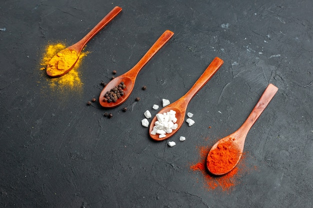 Bottom view diagonal row wooden spoons with turmeric black pepper sae salt red pepper powder on black table