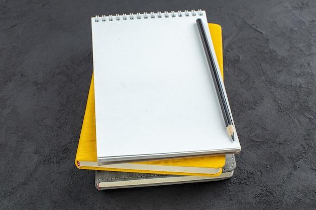 Vista dal basso diversi taccuini e matita nera su sfondo scuro