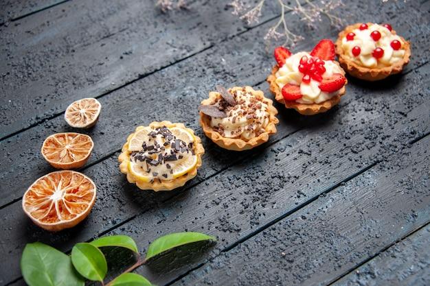 Bottom view different tarts dried oranges leaves on dark background