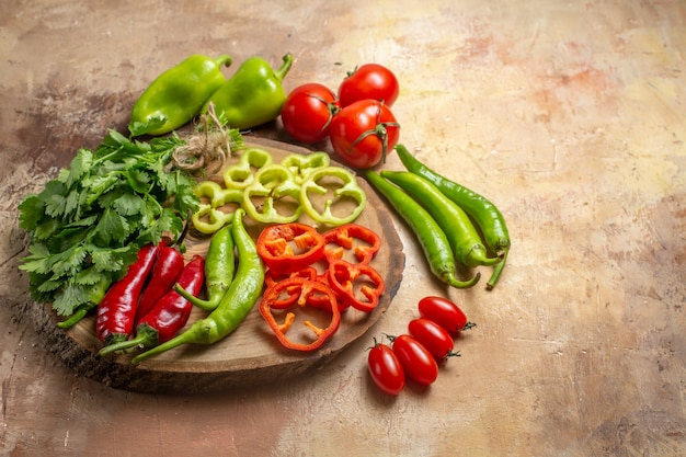 Bottom view different vegetables coriander hot peppers bell peppers cut into pieces on round tree wood board cherry tomatoes on yellow ochre background free space