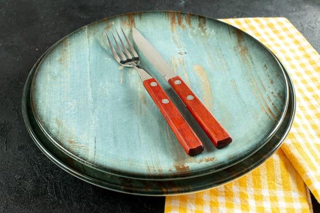 Coltello da pranzo vista dal basso e una forchetta sul piatto sul tovagliolo a scacchi giallo e bianco su fondo nero