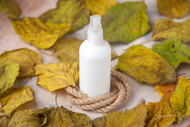 Bottom view empty spray bottle around fall leaves rope on nude background