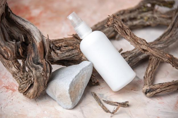 Vista dal basso bottiglia spray vuota ramo di albero pietra su sfondo nudo