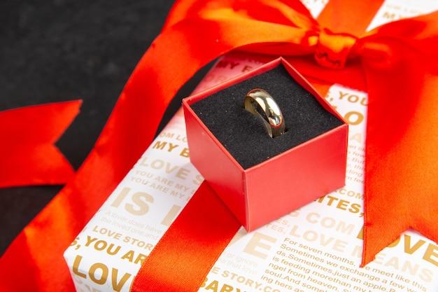 Вид снизу обручальное кольцо в коробке на праздничный подарок на темном фоне