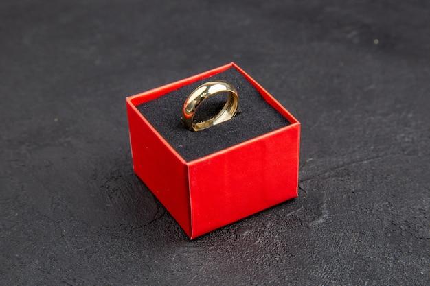 Обручальное кольцо вид снизу в красной коробке на темном фоне