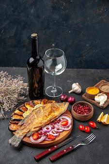 Вид снизу, жареная рыба, жареные баклажаны, нарезанный лук на деревянной сервировочной доске, бутылка вина и стеклянная вилка и нож, чесночные специи на темном фоне